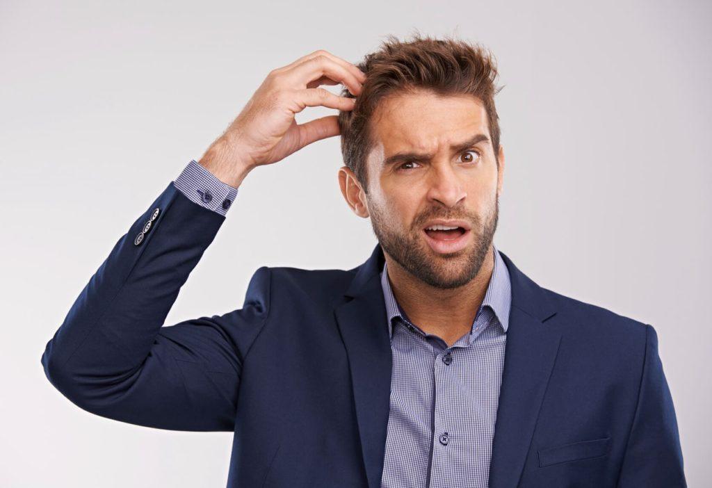 мужчина чешет голову